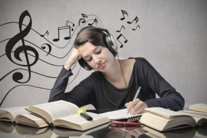 woman writing while using headphone
