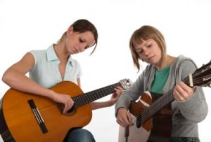 2 people playing guitar