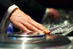 A man's hand touching DJ mixer